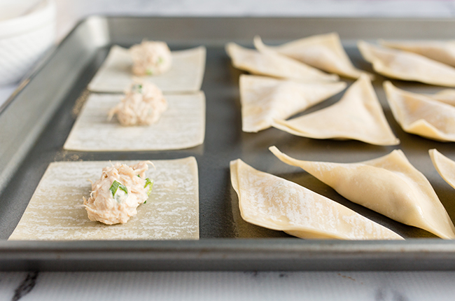 wonton wrappers with filling on a cookie sheet