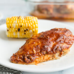 A whole baked chicken breast covered with bbq sauce on a white plate with more chicken in background