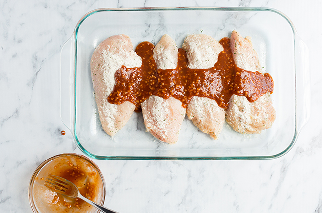 chicken breast with BBQ sauce over top in a baking dish