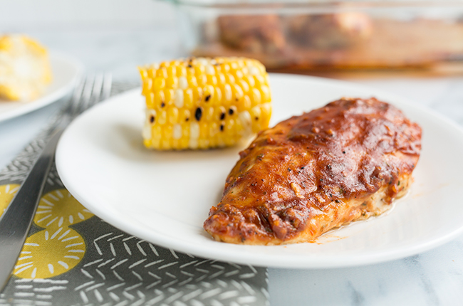 White plate of bbq baked chicken with grilled corn sitting on a gray and yellow cloth napkin