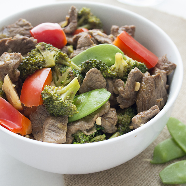 Up close picture of a white bowl of beef stir fry with vegetables