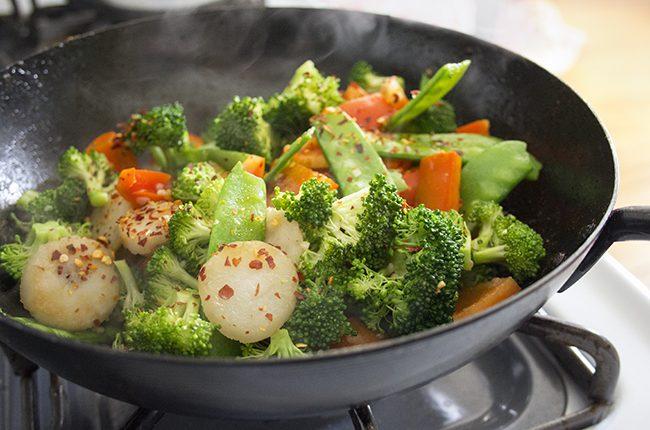 A large black wok filled with stir fry vegetables