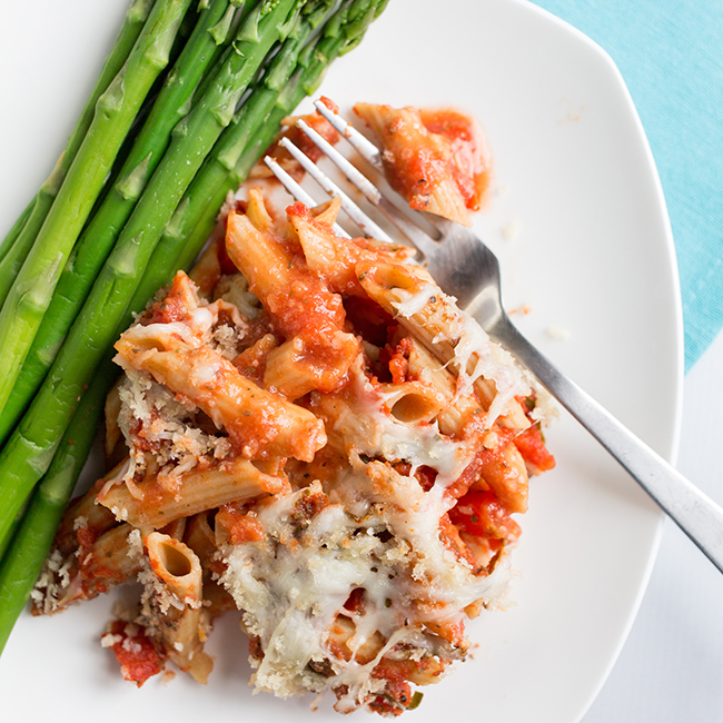 chicken parmesan casserole on a white plate with asparagus