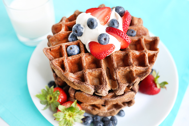 Large white plate of protein powder waffles with glass of milk in background