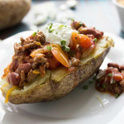Healthier chili cheese baked potato on a white plate