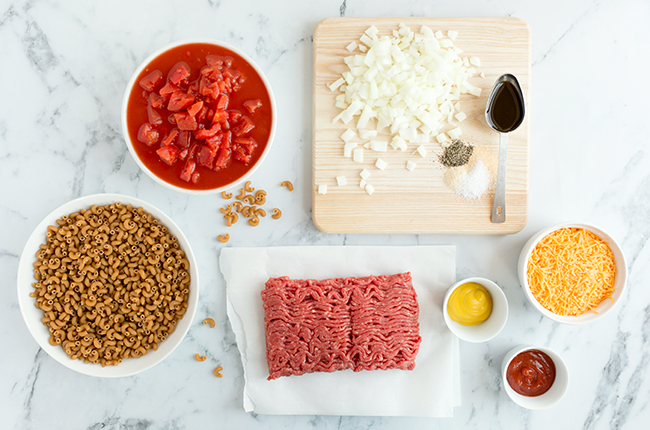 Ingredients for cheeseburger casserole sitting on a marble counter