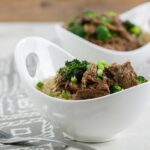 Square picture of Mongolian beef in large white bowl with brown rice
