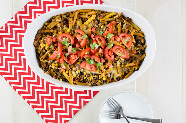 Overhead picture of a tex mex casserole on a red and white chevron cloth