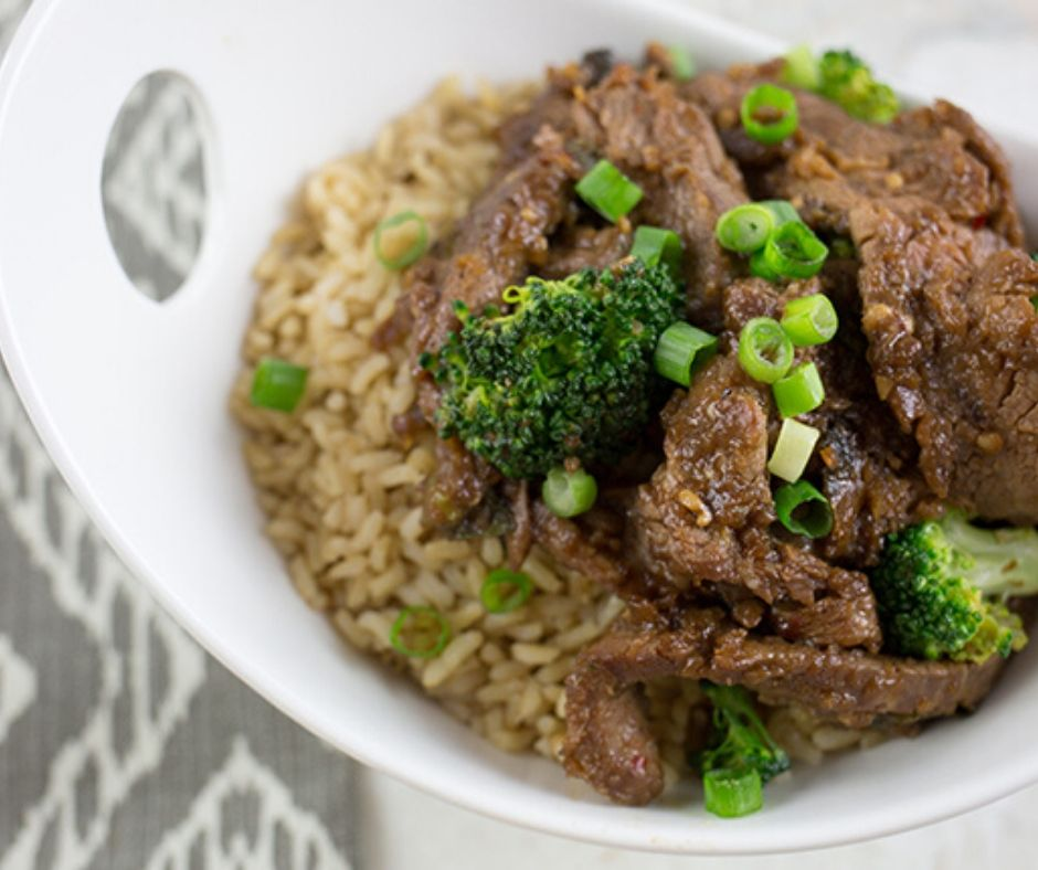 Up close picture of beef strips with broccoli in a bowl over brown rice