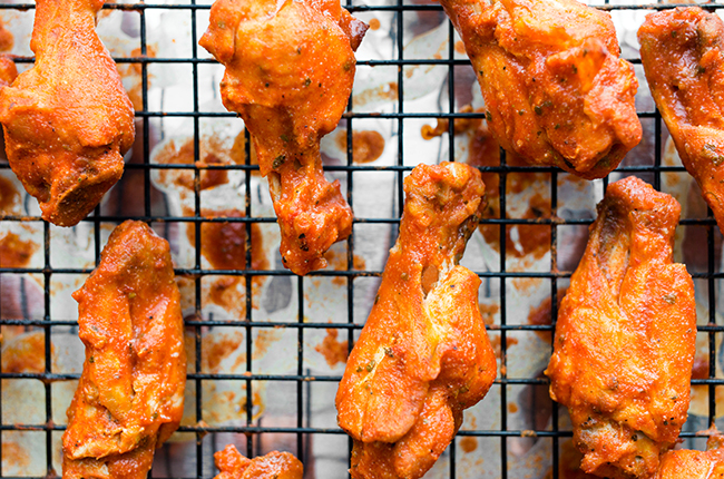 Up close picture of buffalo chicken wings on a wire rack