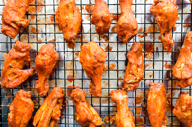 Overhead picture of a baking tray with wire rack holding buffalo chicken wings that have been baked