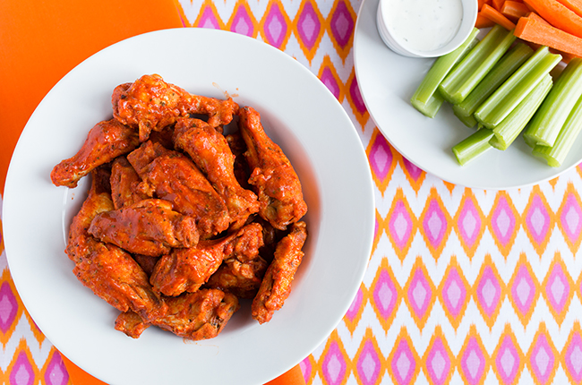 Overhead picture of buffalo chicken wings in a large white bowl sitting on a colorful tablecloth