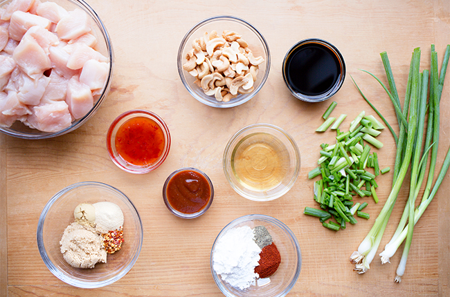 Ingredients for slow cooker cashew chicken recipe in bowls on wooden table
