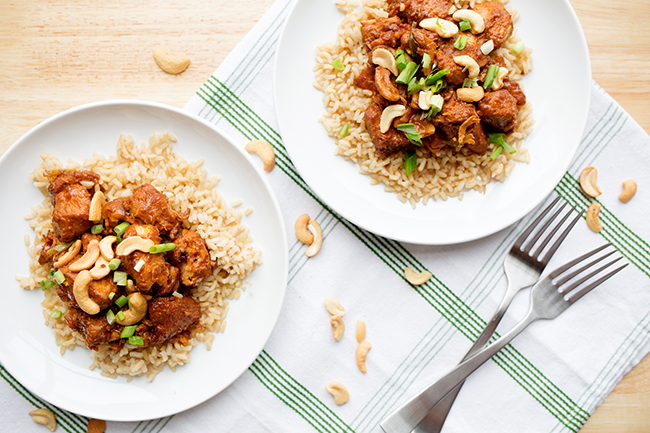 Two plates of cashew chicken recipe on a green and white cloth napkin