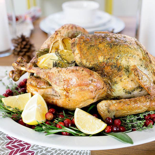 A roasted thanksgiving turkey sitting on a large white platter ready to serve