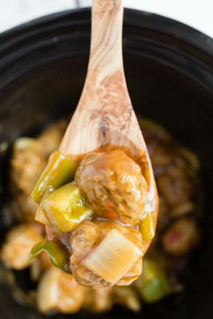 Up close picture of a wooden spoon over a slow cooker holding general tsos chicken