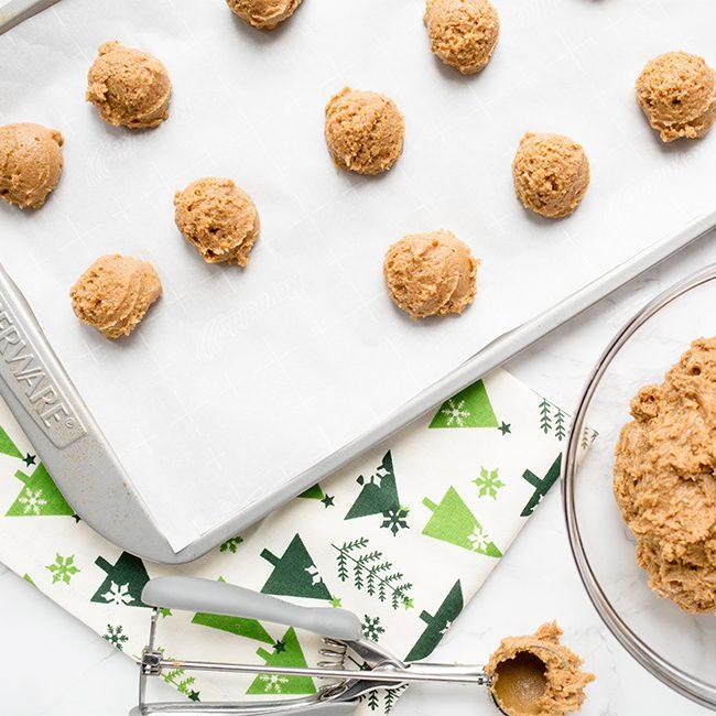 gingerbread cookie dough balls on a baking sheet