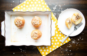Overhead picture of baked apples in white baking dish sitting on yellow cloth