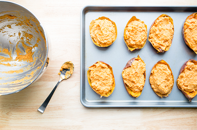 Adding the filling to twice baked sweet potatoes before baking