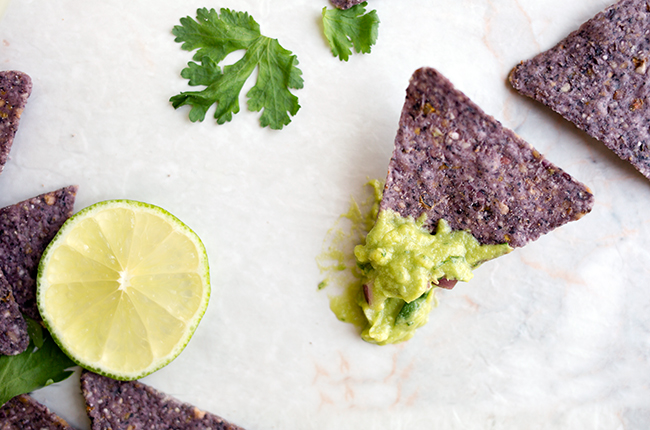 Overhead picture of a blue corn tortilla chip with guacamole