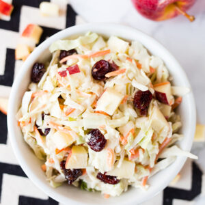 Cranberry Apple Coleslaw in a small white bowl sitting on a black and white chevron napkin
