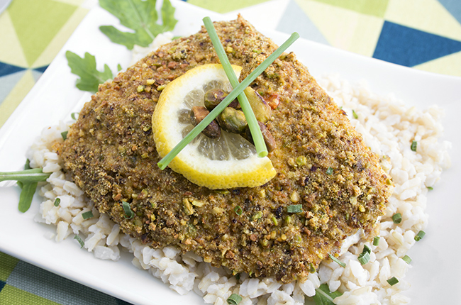 Pistachio baked halibut recipe on a white plate on a blue and green cloth