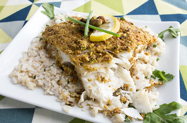 Pistachio crusted baked halibut sitting on a white plate with lemon on top