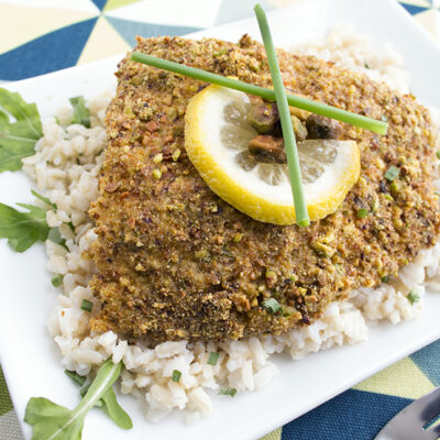 Square image of a pistachio crusted baked halibut on a white plate topped with lemon