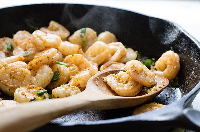 how to make shrimp and grits close up of shrimp in skillet