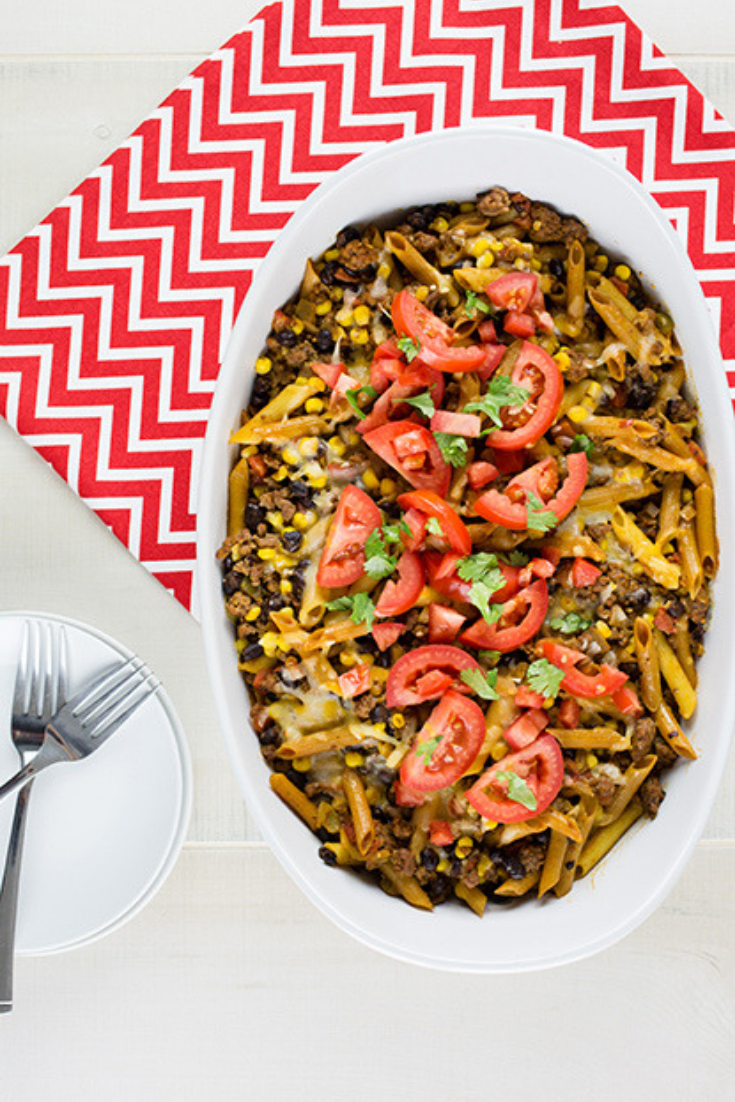 An overhead picture of tex mex pasta casserole sitting on a red and white chevron cloth