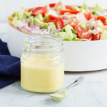 honey mustard dressing in mason jar with spoon and salad in bowl