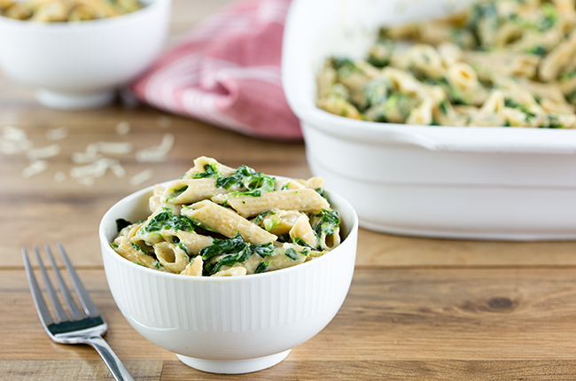 spinach pasta in a white bowl sitting in front of large white baking dish