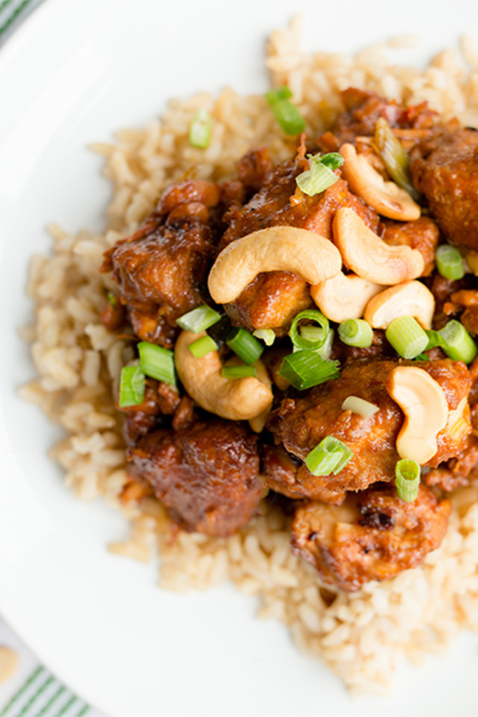 Slow Cooker Cashew Chicken on a white plate topped with cashews and green onions
