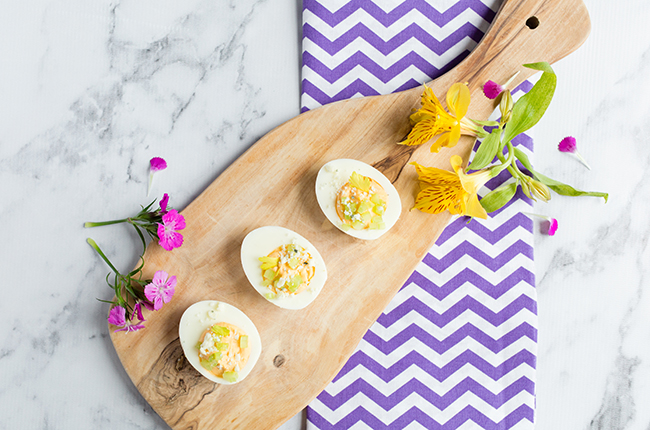 buffalo deviled eggs on a cutting board with a purple and white towel