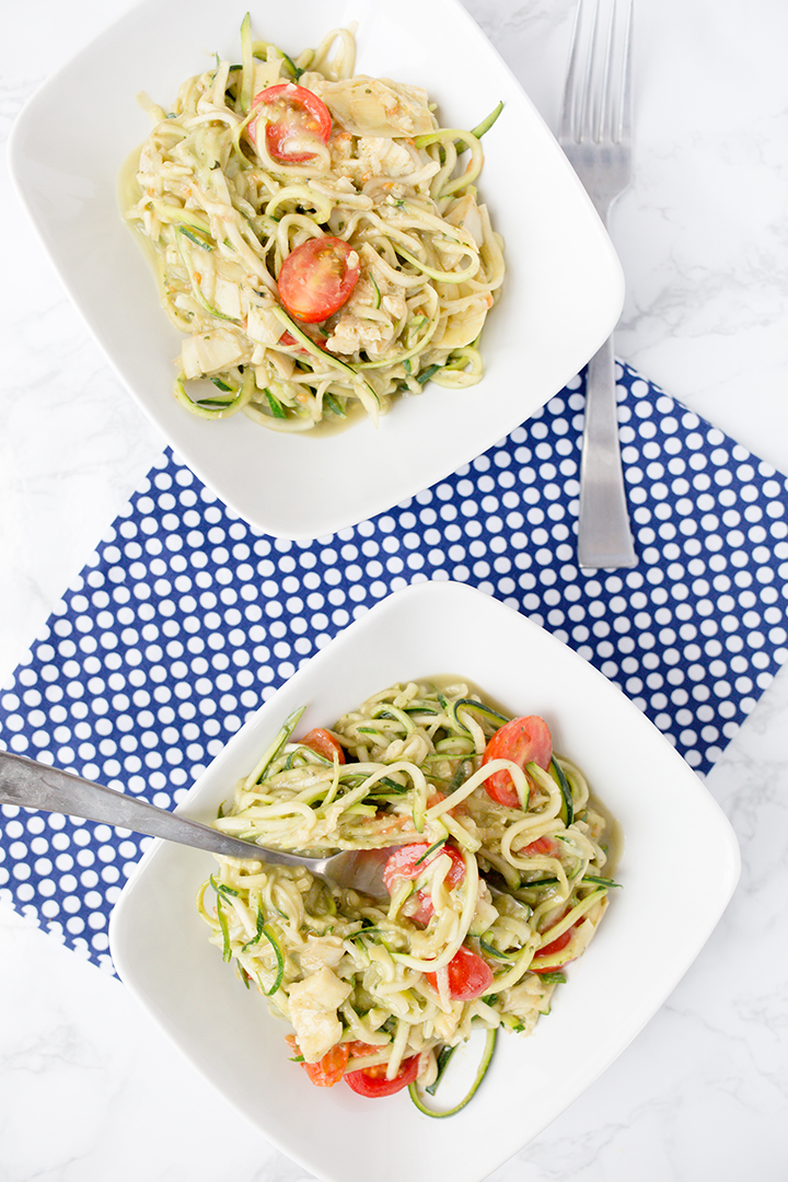 Two bowls of creamy avocado pasta with zoodles sitting on a white table with blue and white cloth