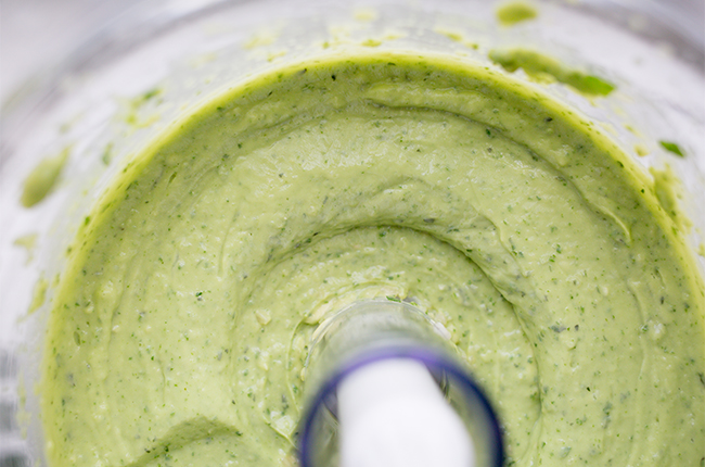 Avocado sauce in a food processor being blended