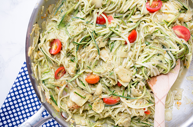 Skillet filled with zoodles tomatoes and avocado cream sauce for pasta