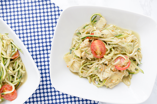 Creamy Avocado pasta made with zoodles and cherry tomatoes sitting in a white bowl on top of a blue checked cloth