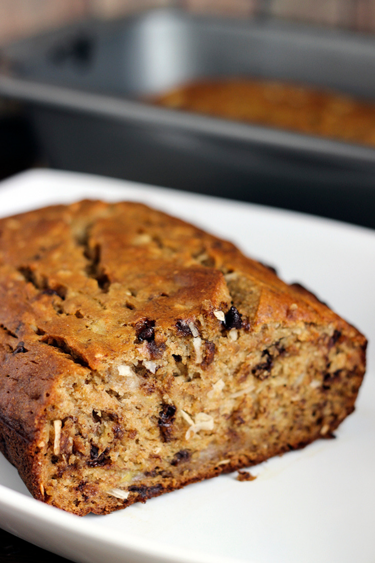 A loaf of coconut banana bread with chocolate chips on a white plate