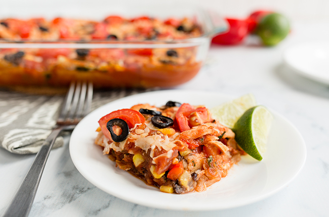 A single serving of mexican lasagna in front of the full casserole