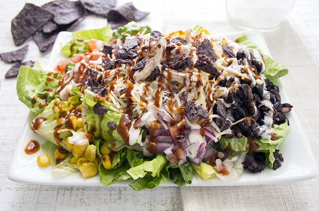 An up close picture of a plate of barbecue chicken salad topped with onions black beans corn and shredded chicken
