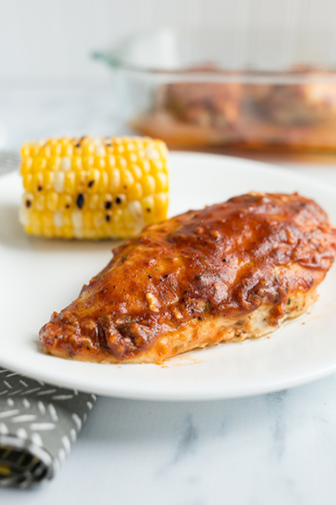 Baked chicken with bbq ranch seasoning on a white plate with grilled corn