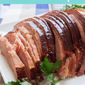 Brown sugar spiral ham in slow cooker sliced and served on white platter