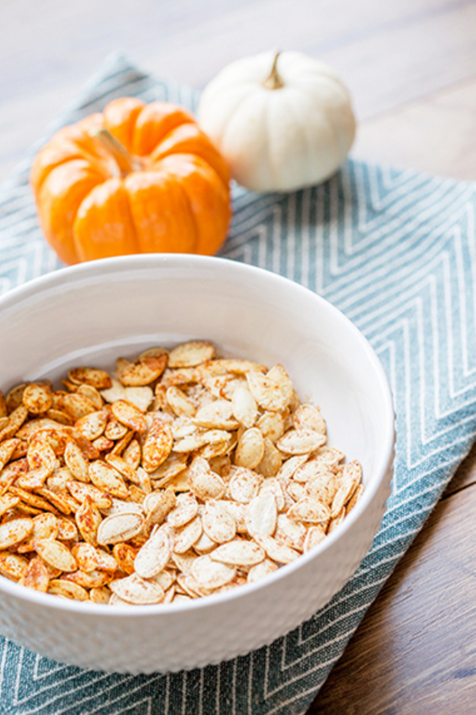 Large white bowl filled with two flavors of roasted pumpkin seeds sitting on a blue napkin