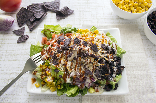 Overhead picture of a large bbq chicken salad on a white plate with ingredients on the sides