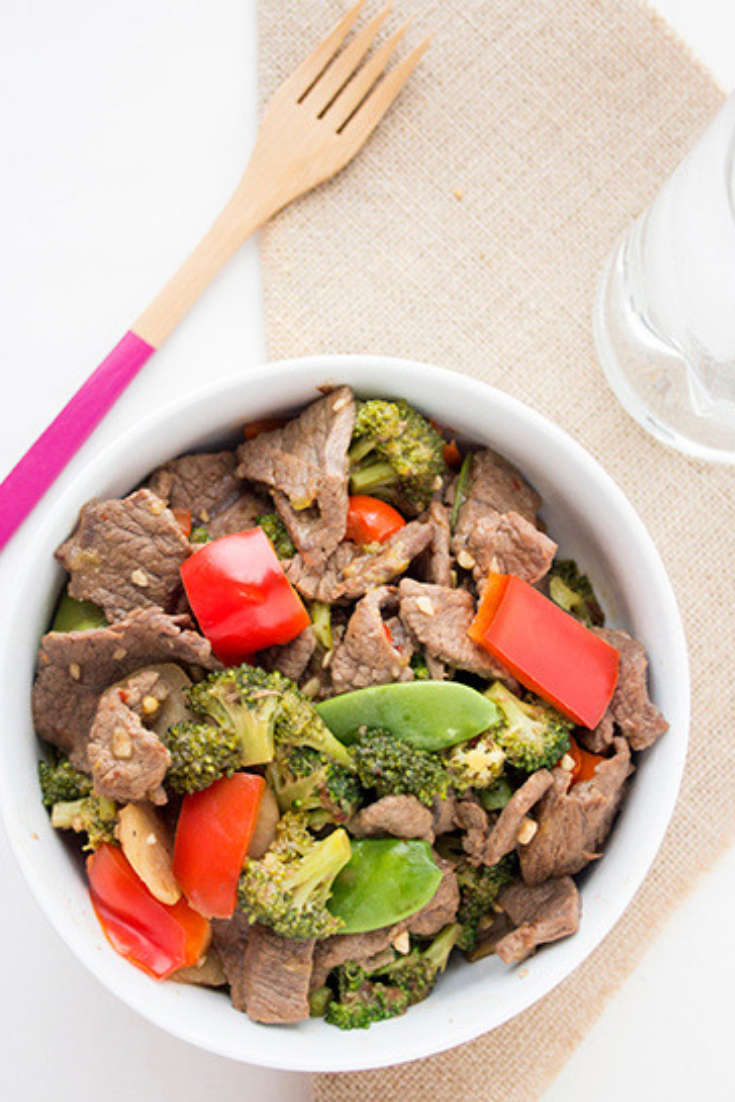 Overhead picture of a large white bowl of Chinese beef stir fry sitting on a burlap napkin with wooden knife in background