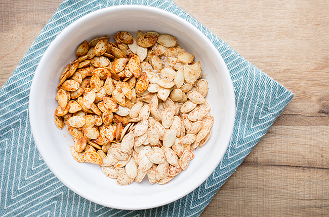 Overhead picture of pumpkin seeds in a white bowl on a blue napkin