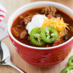 Red bowl filled with turkey chili on a wooden table