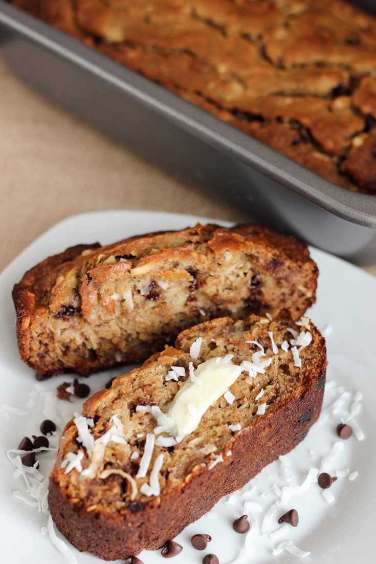 Sliced banana bread with coconut and chocolate chips on a white plate