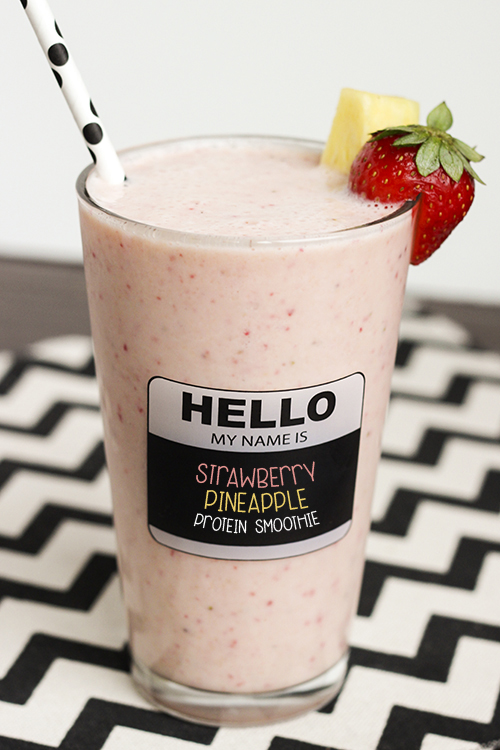 Tall glass of strawberry pineapple smoothie on a black and white chevron cloth